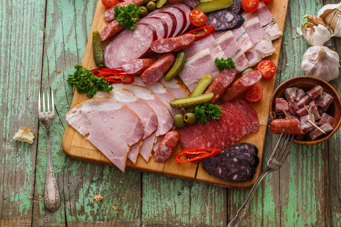 Charcuterie board with sausages and smoked meat. Top view