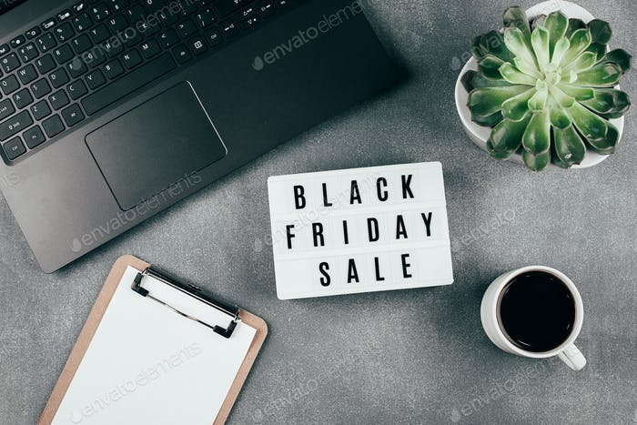 Black friday sale word on lightbox, laptop, coffee, empty blank, succulent plant on table. Flat lay