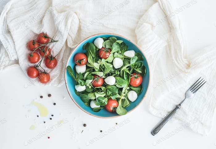 Spring salad with lamb's lettuce, mozarella and cherry-tomatoes in blue ceramic bowl