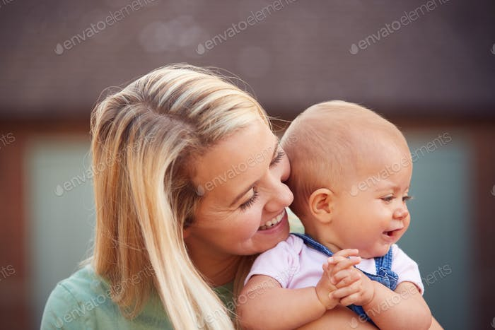 Loving Mother Cuddling Smiling Baby Daughter Outside House