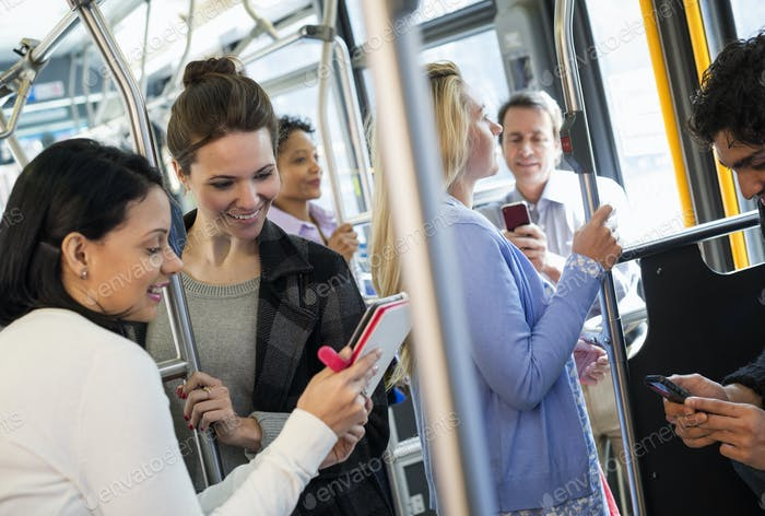 Männer und Frauen im Stadtbus. Öffentliche Verkehrsmittel. Zwei Frauen schauen sich ein digitales Handheld Tablet an.