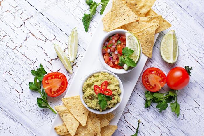Guacamole, tomato sauce salsa and chips nachos