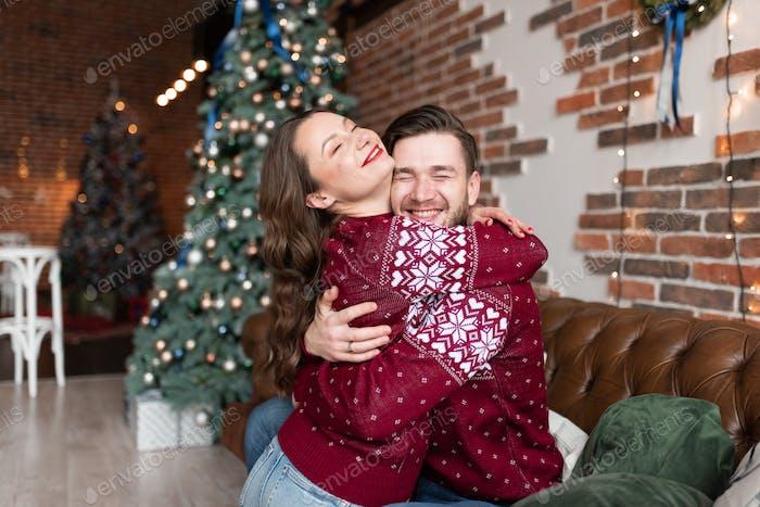 Esposo y mujer en suéteres de punto idénticos se divierten juntos celebrando la Navidad.