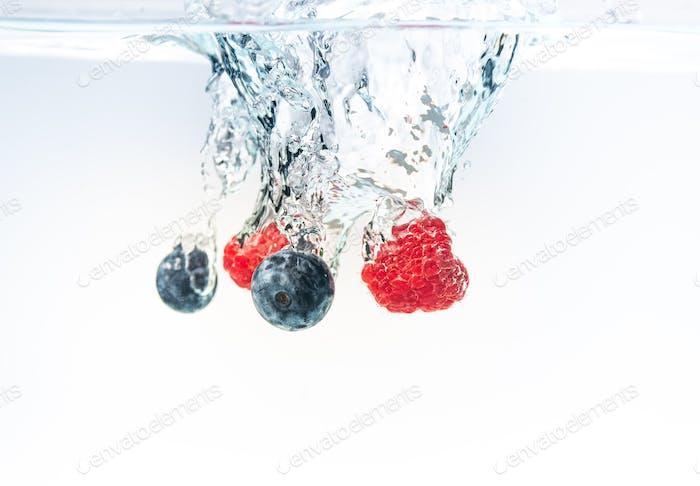 Heidelbeere und Himbeeren spritzen in kristallklares Wasser mit Luftblasen