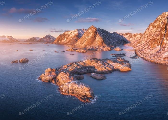 Luftaufnahme von Felsen im Meer, verschneite Berge, blauer Himmel