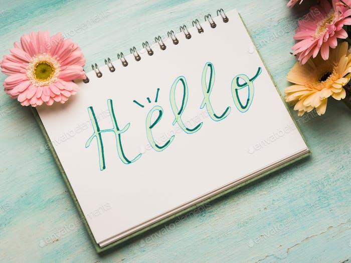 Hola palabra escrita en la página del cuaderno. Flores de jardín