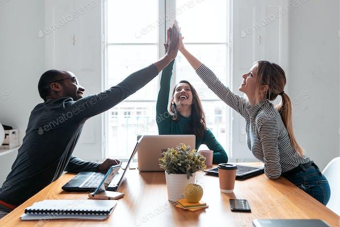 Grupo de jóvenes empresarios exitosos que sostienen sus manos derechas en el lugar de coworking.