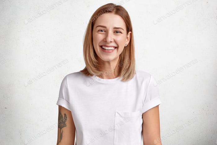 Horizontal shot of adorable Caucasian female with positive expression, has white perfect teeth, heal