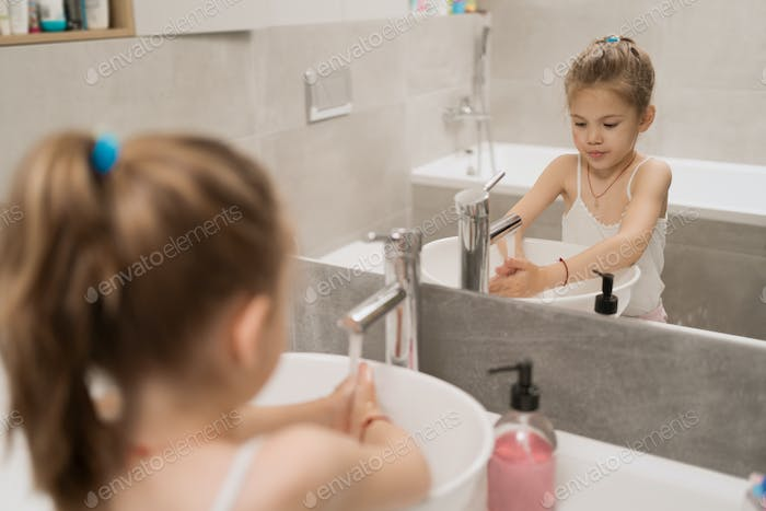 Little girl washing hands with soap