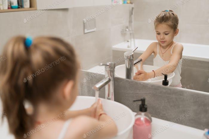Маленькая девочка мыла руки с мылом