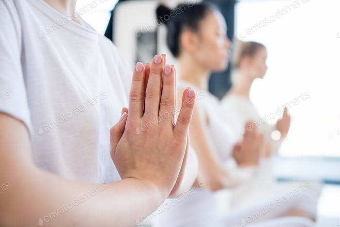Concentrated young women meditating in lotus pose with Namaste mudra gesture indoors