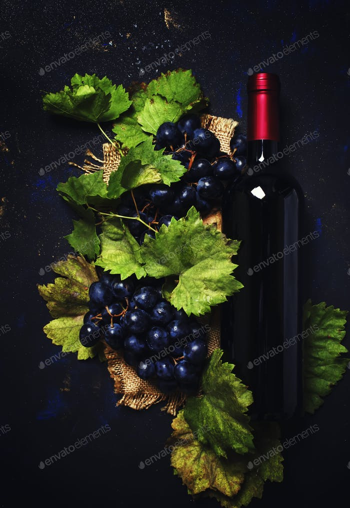 Red wine in bottle and grapes