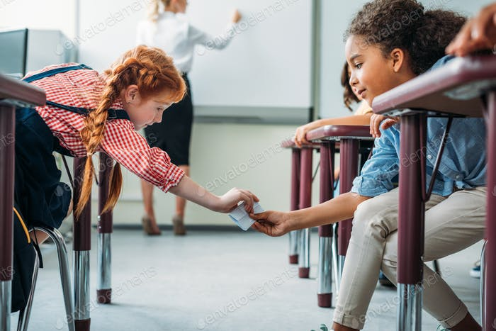 schoolgirls passing message in class on lesson
