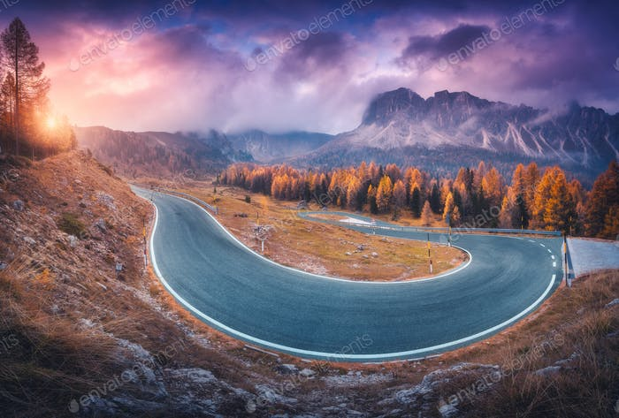 Asphalt winding road in mountains at colorful sunset in autumn