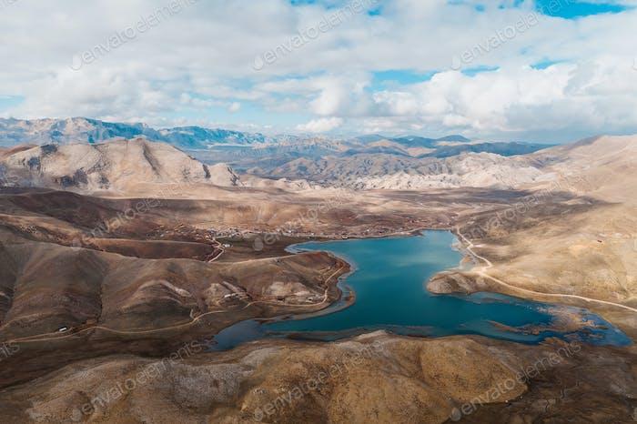 Luftaufnahme von felsigen Bergen mit einem See auf der Oberseite