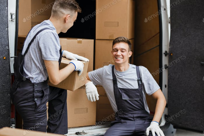 Two young handsome movers wearing uniforms are laughing while unloading the van full of boxes. House