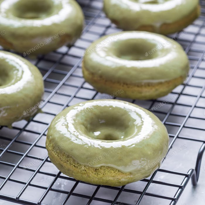 Freshly baked matcha banana donuts with matcha citrus glaze on cooling rack, square format
