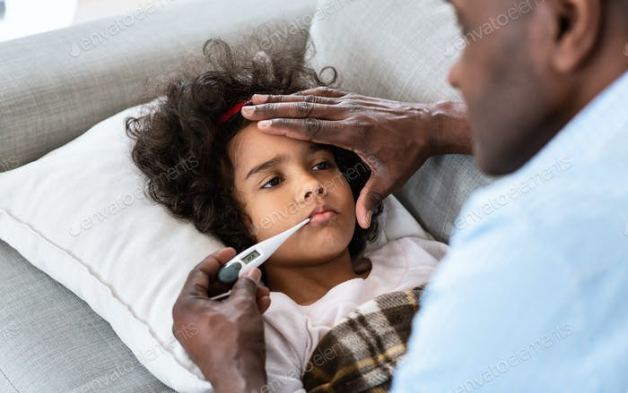 Health alert. Grandfather treating his sick little granddaughter at home