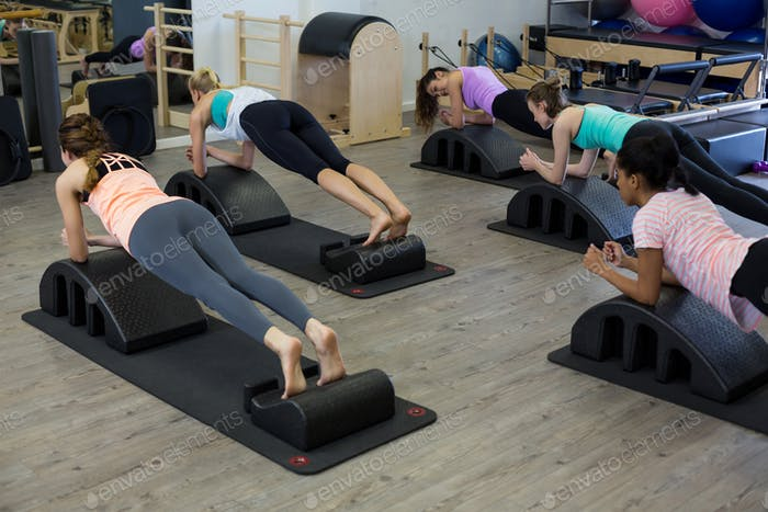 Fit women exercising on arc barrel