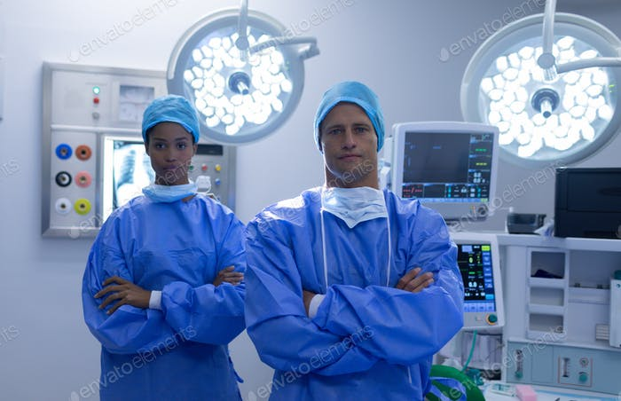 Front view of diverse surgeons standing together with arms crossed in operation theater at hospital
