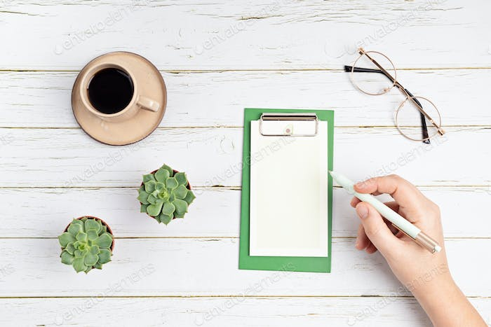 Blank notepad with pen and glasses on white wooden background