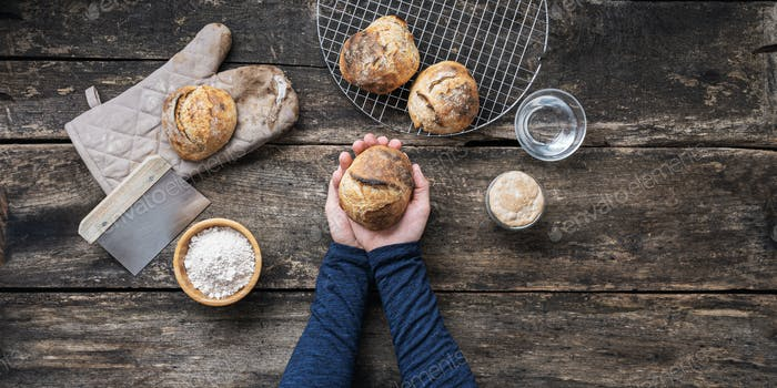 Top view of male hands holding fresh home made bread bun