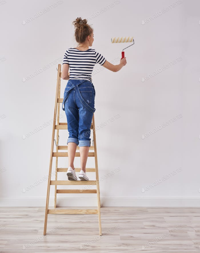 Rear view of young woman with paint roller painting wall