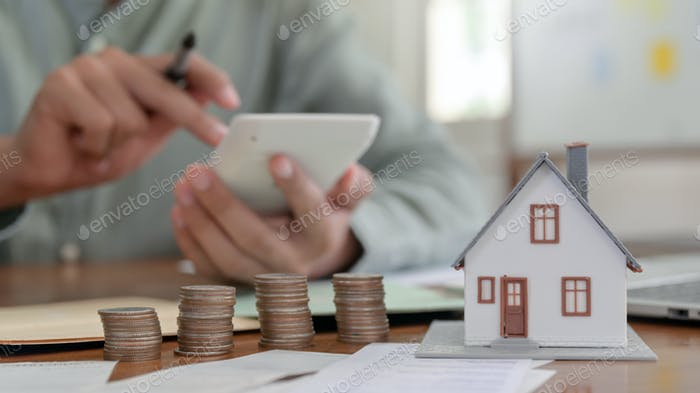 Close-up shot of Houses models and coins with people using a calculator to calculate home expenses.