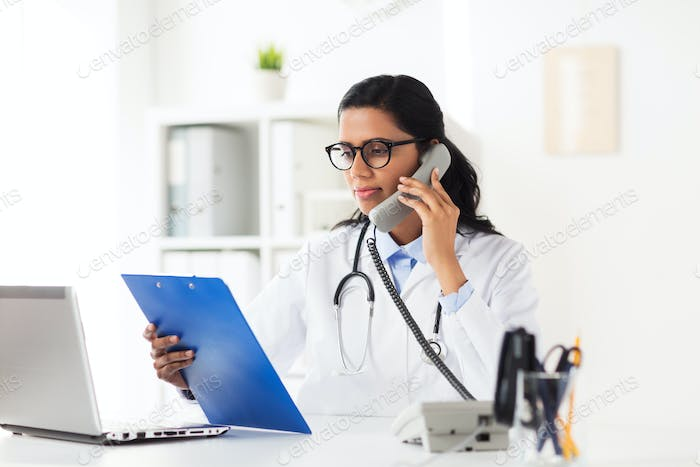 doctor with clipboard calling on phone at hospital