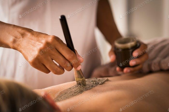 Beautician applying mud on body