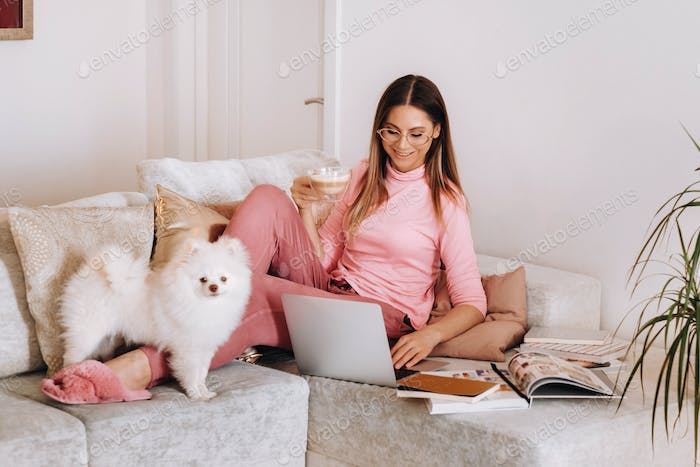 a girl in pajamas at home is working on a laptop with her dog Spitzer, the dog and its owner are