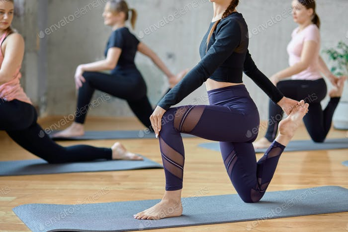 Crop of women practicing yoga in hall
