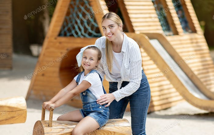 Happy Mother And Little Daughter Having Fun On Playground Outside