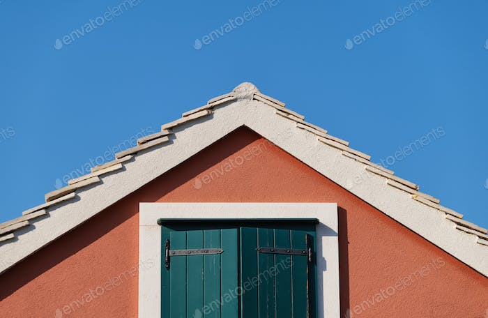 The house on the blue sky background. Roof and window with shutters.