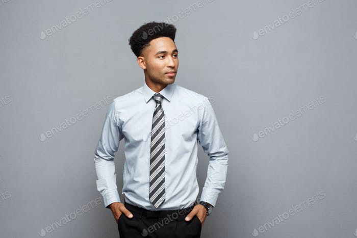 Business Concept - Happy confident professional african american businessman posing over grey