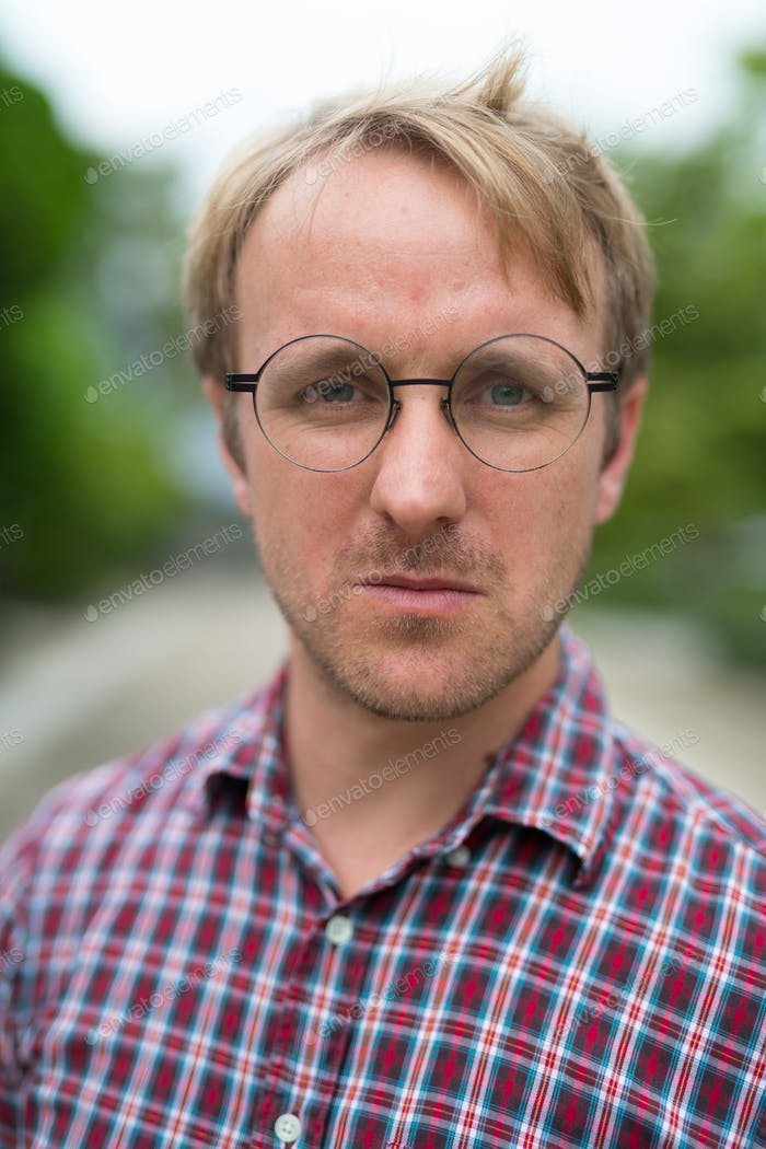 Portrait of man with blonde hair wearing eyeglasses outdoors