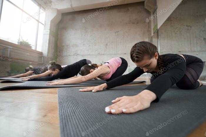 Gruppe von Mädchen tun Stretching Übung in der Halle
