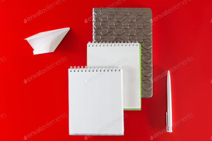 Minimalistic layout for design. Office supplies - notebooks and pens on a red background.