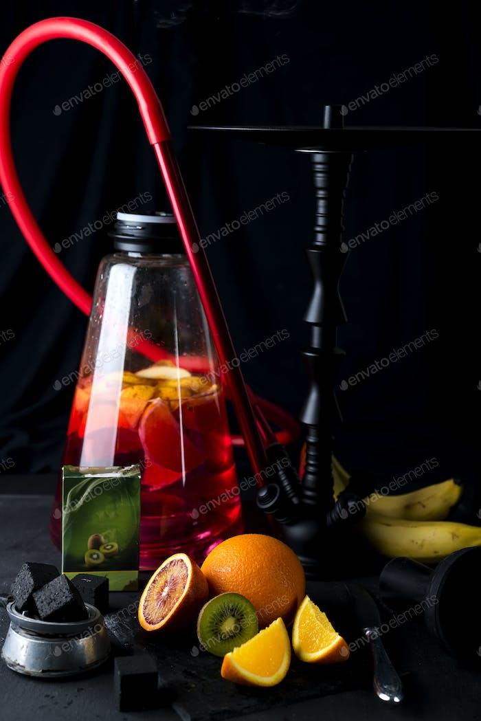 Red hookah with orange slice on a black background