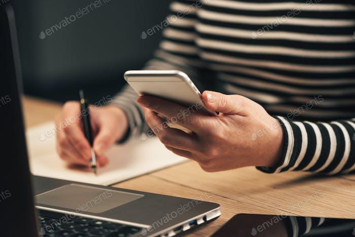 Frau, die Kontaktliste vom Telefon in die Business-Agenda schreibt