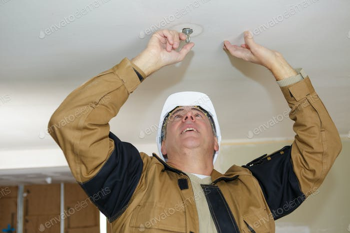middle-age electrician fixes halogen lamp in ceiling light in room