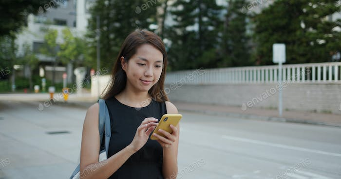 Woman use of smart phone and walk in the street