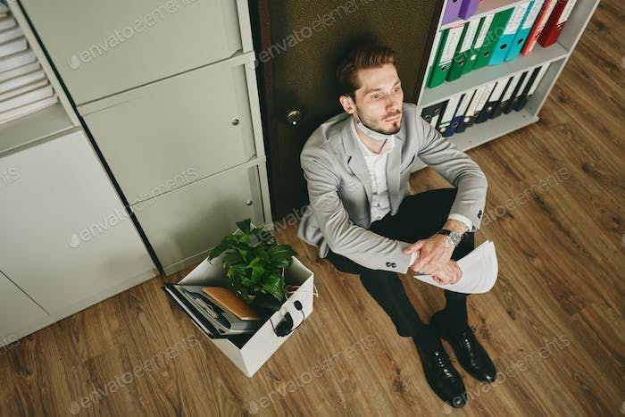 Stressed young broker with papers sitting by safe during crisis after quarantine
