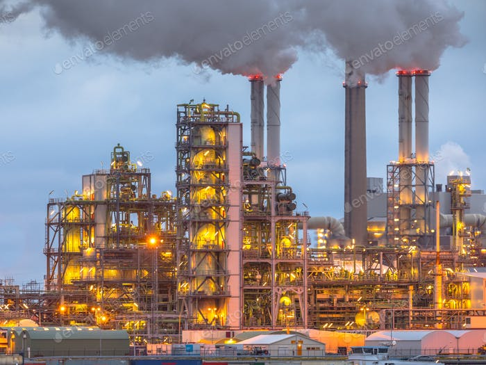 Chemical plant at dusk with lights and smoke