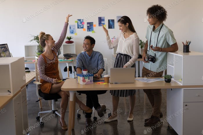 Business colleagues interacting with each other and smiling in office