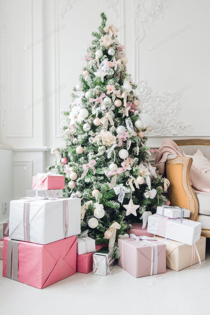 Beautiful modern design of the room in delicate light colors decorated with Christmas tree