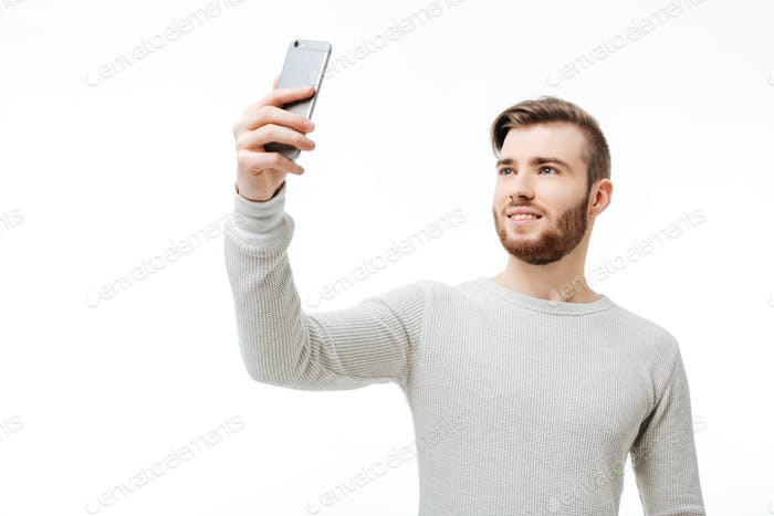Happy casual man taking selfie over white background