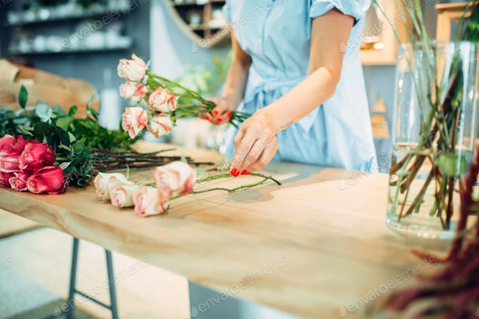 Florist makes rose composition in flower shop