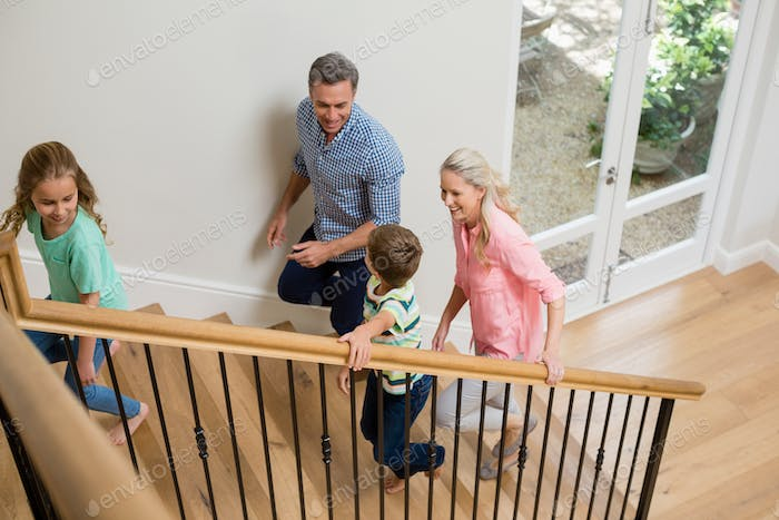 Parents and kids walking upstairs at home