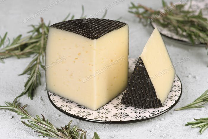 piece of Spanish sheep cheese on a plate with rosemary on a granulated rustic background